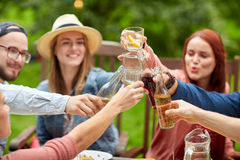 Happy friends with drinks at summer garden party. Leisure, holidays, eating, people and food concept - happy friends having dinner at summer garden party and Stock Photography