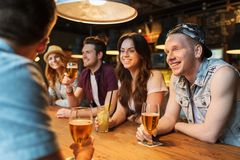 Happy friends with drinks talking at bar or pub Royalty Free Stock Images