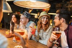 Happy friends with drinks talking at bar or pub Stock Photos