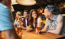 Happy friends with drinks talking at bar or pub. People, leisure, friendship and communication concept - group of happy smiling friends drinking beer and Royalty Free Stock Photos