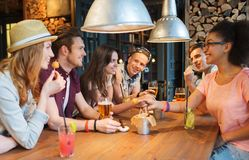 Happy friends with drinks talking at bar or pub. People, leisure, friendship and communication concept - group of happy smiling friends drinking beer and Stock Photography