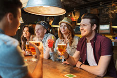 Happy friends with drinks talking at bar or pub. People, leisure, friendship and communication concept - group of happy smiling friends drinking beer and Royalty Free Stock Photo