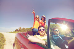 Happy friends driving in cabriolet car at country. Leisure, road trip, travel and people concept - happy friends driving in cabriolet car along country road and Stock Photography