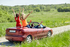 Happy friends driving in cabriolet car at country Stock Image