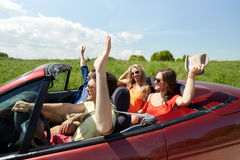 Happy friends driving in cabriolet car at country Royalty Free Stock Photos