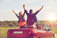 Happy friends driving in cabriolet car at country Stock Photo
