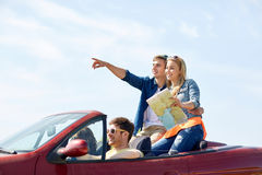 Happy friends driving in cabriolet car Stock Images