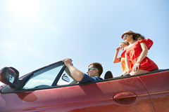Happy friends driving in cabriolet car outdoors Stock Photography
