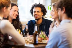 Happy friends eating at bar or restaurant. Leisure and people concept - happy friends eating and drinking non-alcoholic drinks at bar or restaurant stock photography