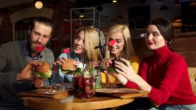 Four friends eat hamburgers and drink lemonade in a bright Sunny cafe. Happy friends are eating burgers, talking and smiling while spending time together in stock video footage