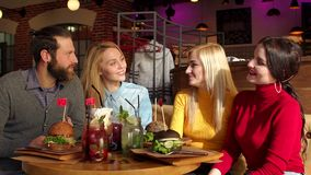 Four friends eat hamburgers and drink lemonade in a bright Sunny cafe. Happy friends are eating burgers, talking and smiling while spending time together in stock footage