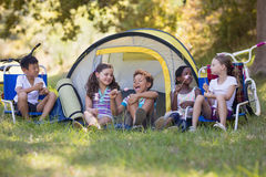 Happy friends eating candies while sitting outside tent Stock Photography