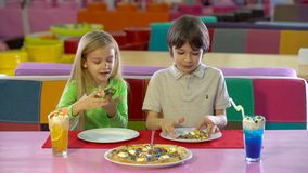 Happy friends eating chocolate pizza at children`s entertainment center. Happy friends enjoy eating chocolate pizza during lunch at children`s entertainment stock video