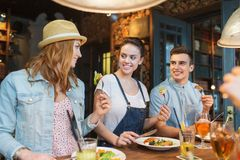 Happy friends eating and drinking at bar or pub Royalty Free Stock Images