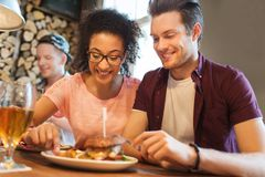 Happy friends eating and drinking at bar or pub Royalty Free Stock Photo