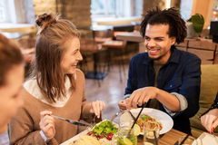 Happy friends eating and drinking at restaurant. Leisure, food, drinks, people and holidays concept - happy friends eating and drinking at restaurant royalty free stock photos