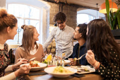 Happy friends eating and drinking at restaurant. Leisure, food, drinks, people and holidays concept - happy friends eating and drinking at restaurant royalty free stock image