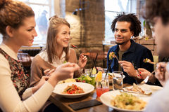 Happy friends eating and drinking at restaurant. Leisure, food, drinks, people and holidays concept - happy friends eating and drinking at restaurant stock photography