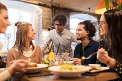 Happy friends eating and drinking at restaurant. Leisure, food, drinks, people and holidays concept - happy friends eating and drinking at restaurant royalty free stock photo
