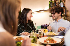 Happy friends eating and drinking at restaurant. Leisure, food, drinks, people and holidays concept - happy friends eating and drinking at restaurant stock photos