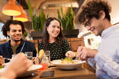 Happy friends eating and drinking at restaurant. Leisure, food, drinks, people and holidays concept - happy friends eating and drinking at restaurant royalty free stock photography