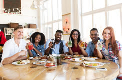 Happy friends eating and drinking at restaurant. Leisure, food and people concept - group of happy international friends with drinks eating at restaurant table royalty free stock photo