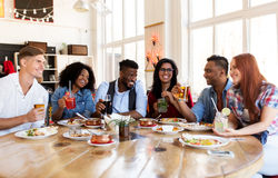 Happy friends eating and drinking at restaurant. Leisure, food and people concept - group of happy international friends with drinks eating and talking at royalty free stock photography