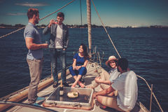 Happy friends eating fruits and drinking on a yacht Royalty Free Stock Image