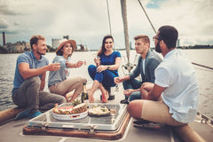 Happy friends eating fruits and drinking on a yacht Royalty Free Stock Photography