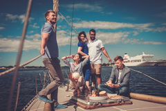 Happy friends eating fruits and drinking on a yacht Royalty Free Stock Photo