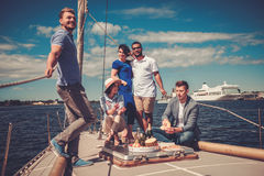 Happy friends eating fruits and drinking on a yacht Royalty Free Stock Photos