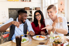 Happy friends eating and having fun at restaurant. Leisure, food and people concept - group of happy international friends eating and having fun at restaurant Stock Image