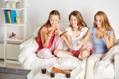 Happy friends eating pizza and watching tv at home Stock Image
