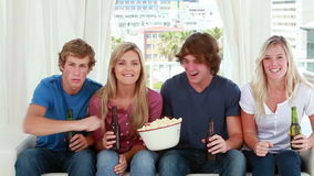 Happy friends eating popcorn while sitting Stock Images