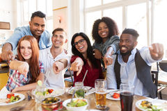 Happy friends eating at restaurant Stock Image