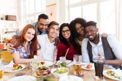 Happy friends eating at restaurant. Leisure, food and people concept - group of happy international friends eating at restaurant table royalty free stock photography