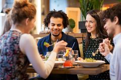 Happy friends eating at restaurant Stock Photography