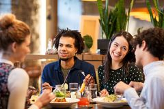 Happy friends eating at restaurant. Leisure and people concept - happy friends eating at restaurant royalty free stock images