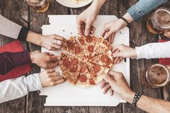 Happy Friends Eating Take Away Pizza And Drinking Beer Stock Image
