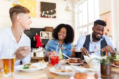 Happy friends eating and talking at restaurant. Leisure, food and people concept - group of happy international friends eating and talking at restaurant table stock photos