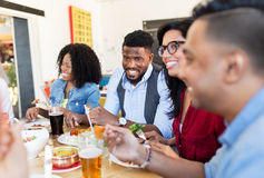 Happy friends eating and talking at restaurant. Leisure, food and people concept - group of happy international friends eating and talking at restaurant table royalty free stock photo