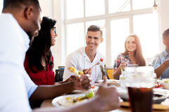 Happy friends eating and talking at restaurant. Leisure, food and people concept - group of happy international friends eating and talking at restaurant table royalty free stock images