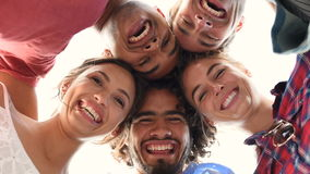 Happy friends embracing. Directly below shot of young friends forming huddle. Low angle view of girls and guys with their head forming a circle. Portrait of stock footage