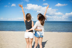 Happy friends embracing each other raising hands on beach Stock Photos