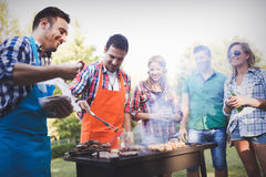 Happy friends enjoying barbecue party. Happy friends grilling meat and enjoying barbecue party outdoors stock photos