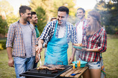 Happy friends enjoying barbecue party. Happy friends grilling meat and enjoying barbecue party outdoors Royalty Free Stock Photo