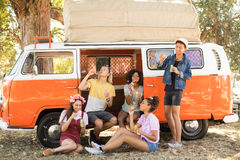 Happy friends enjoying with bubble wand at camper van Stock Image