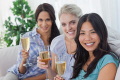 Happy friends enjoying champagne together looking at camera. At home on couch Stock Photography