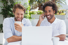 Happy friends enjoying coffee together with laptop Royalty Free Stock Image