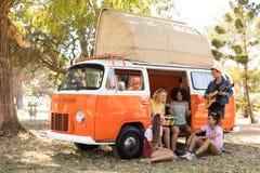Happy friends enjoying music at camper van Stock Photos